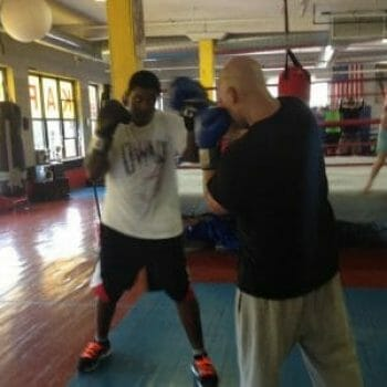 boxers doing boxing drills with girl in background